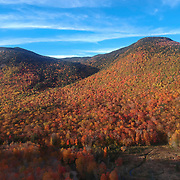 Peak fall colors adorn the southern Presidential range of the White Mtn. Ntl Park. The saco River begins its journey to the Atlantic. Photo from elevation 400 ft.