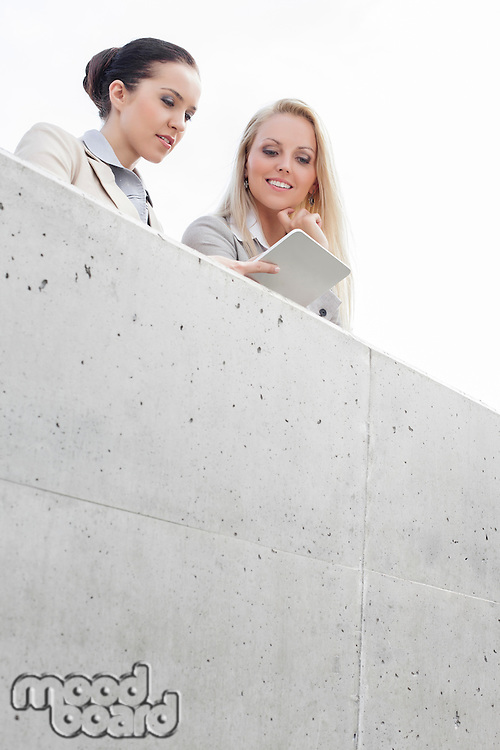 Low angle view of young female business executives using digital tablet while standing on terrace against sky