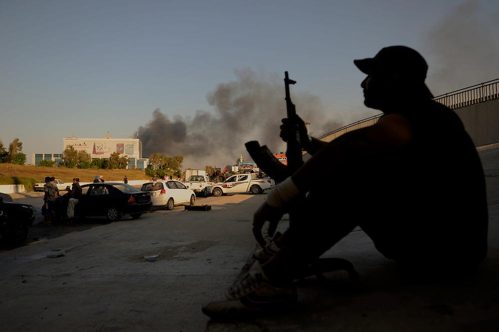 A rebel fighter takes a rest as smoke raises in the sky after a NATO attack to Muammar Gaddafi's stronghold of Bab Al Azizia compound in Tripoli.