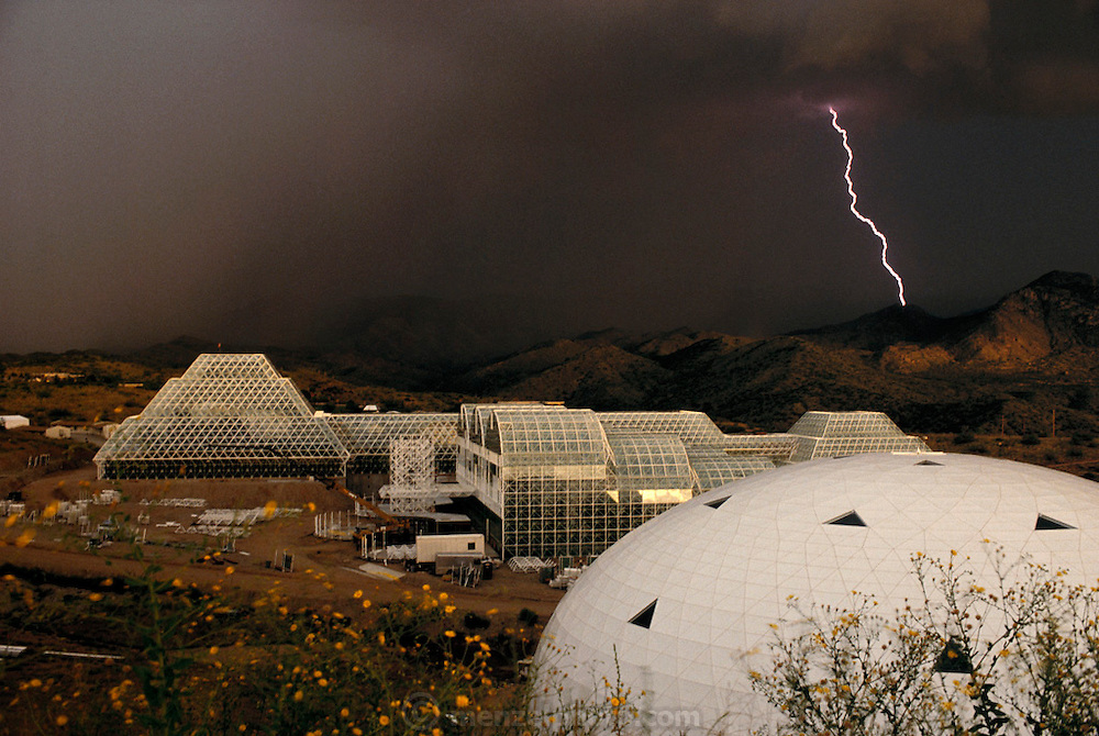 Biosphere 2 Project buildings seen at late afternoon with lightning bolt in the sky. The Biosphere was a privately funded experiment, designed to investigate the way in which humans interact with a small self-sufficient ecological environment, and to look at possibilities for future planetary colonization. This photograph won World Press First Place Science photo in 1991. 1990