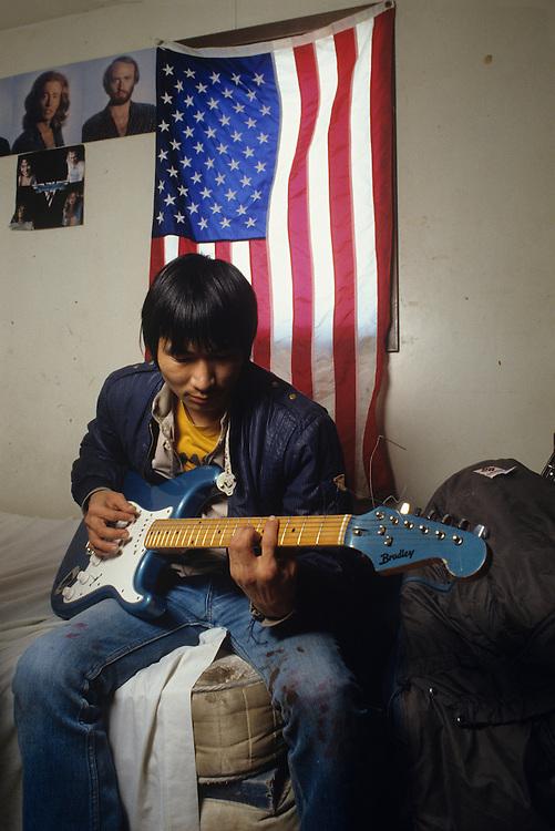 USA, Alaska, Yupik Eskimo Murphy Fairbanks plays guitar in his home in Bering Sea village of Tununak