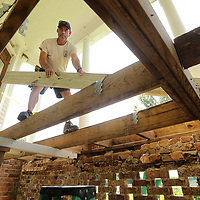 Ronnie Schutkesting, Facilities Director at the Private John Allen Fish Hatchery, works on placing new support beams in place for new composite decking to be installed on the front porch of the Fish Hatchery home in Tupelo on Wednesday morning.