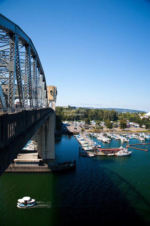 The Burrard St. Bridge passes over English Bay.  A water taxi below the bridge.