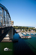 The Burrard St. Bridge passes over English Bay.  A water taxi below the bridge.
