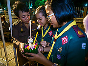 "03 NOVEMBER 2017 - BANGKOK, THAILAND:  Girl Scouts pray before floating their krathong during Loi Krathong at Wat Prayurawongsawat on the Thonburi side of the Chao Phraya River. Loi Krathong is translated as ""to float (Loi) a basket (Krathong)"", and comes from the tradition of making krathong or buoyant, decorated baskets, which are then floated on a river to make merit. On the night of the full moon of the 12th lunar month (usually November), Thais launch their krathong on a river, canal or a pond, making a wish as they do so. Loi Krathong is also celebrated in other Theravada Buddhist countries like Myanmar, where it is called the Tazaungdaing Festival, and Cambodia, where it is called Bon Om Tuk.    PHOTO BY JACK KURTZ"