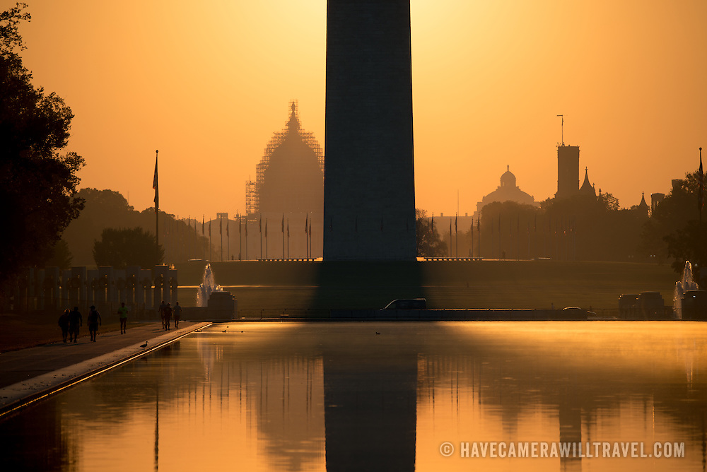 WASHINGTON, DC--The rising sun reflects off the still waters of the Reflecting Pool, looking east towards the Washington Monument and US Capitol Dome in the distance.