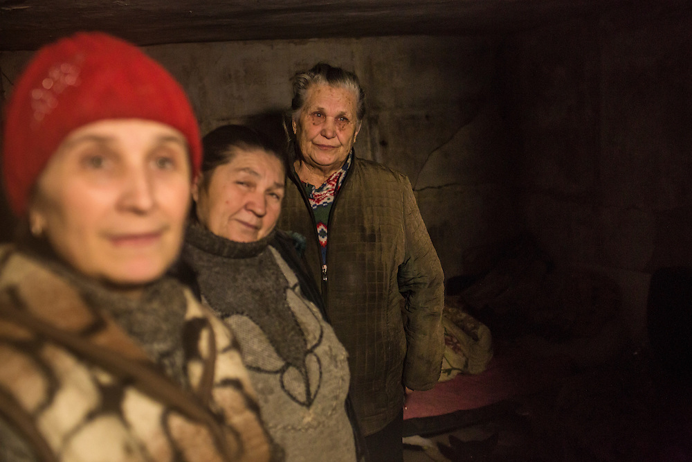 DONETSK, UKRAINE - FEBRUARY 3, 2015: Neighbors Valentina Anosikova, 53, Vera Dmitrenko, 67, and Alla Kozikova, 81, from left, gather in the basement shelter in which they've been living for days in the Petrovsky district of Donetsk, Ukraine. The neighborhood has been under heavy shelling for the past four days, and a brief pause allowed a few residents to leave their basement hiding places for some fresh air. CREDIT: Brendan Hoffman for The New York Times