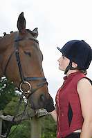Girl in riding hat holding horse