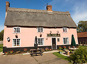 Thatched historic country pub building, The Crown, Bedfield, Suffolk, England, UK pink wash exterior