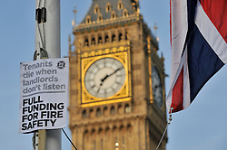 © Licensed to London News Pictures. 19/06/2017. London, UK. A sign affixed to a flagpole as people gather for a vigil in Parliament Square to remember those who died in the Grenfell Tower fire in North Kensington of 14 June.  Mourners and wellwishers were given the opportunity to speak and to write messages on a community banner.  Photo credit : Stephen Chung/LNP