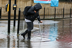 © Licensed to London News Pictures. 15/01/2020. London, UK. A member of public with a crutch walks through a flood on Green Lanes in north London following heavy overnight rainfall. Photo credit: Dinendra Haria/LNP