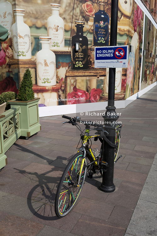 A No Idling Engines sign aimed at waiting black cab drivers, and a locked-up bike at the rear of the Harrods Department Store in Knightsbridge, on 15th April 2019, in London, England.
