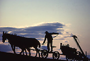 Amish farmer at dusk finishes mowing, Lancaster County, PA