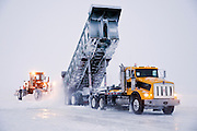 Alaska, North Slope. A maxi haul dumps snow for an awaiting motor grader during ice road construction.