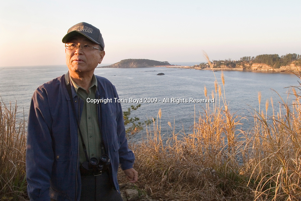 Nov. 26, 2009, Sakai City, Japan: This is 66 year old Isao Saito, a retired police officer from Fukui Prefecture patrolling the rocky cliffs at Tojinbo for possible suicides attempts on November 26, 2009. He is right at the precipice where many have jumped. Mr. Saito is a member of the NPO suicide prevention group Kokoro ni Hibiku Bunshu Henshukyoku, which was founded by 65 year old Yukio Shige (pronounced shee-gay), a retired policeman from Fukui Prefecture who took up his cause in 2004, just before retirement as a police deputy at a nearby police station. When Shige discovered how many suicides were occurring here, he began patrolling the cliffs of Tojinbo in order to spot those contemplating suicide. Upon retirement Shige opened a small cafe at Tojinbo where he also set up his NPO. Since then other volunteers like Mr. Saito have joined his cause and as of November 2009, he and his group have talked 222 out of committing suicide. They do this by patrolling the cliffs daily with binoculars in hand, and when they spot someone they kindly approach them and coax them away to Shige's cafe where they offer them tea and rice cakes. They also see these people home safely, and in cases where an individual is homeless, they find them accommodations. However there are still some that slip past their watchful eyes and so far in 2009 thirteen people have jumped to their deaths here. Japan has one of the highest suicide rates in the world and 2009 may surpass the record 34,427 deaths that occurred here in 2003. This increase is thought to be a result of the Japanese recession which has been worsened by the global economic downturn. Depression is the number one cause for suicide in Japan, followed by illness and debt. Photo by Torin Boyd.