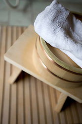 Detail of traditional wooden stool, basin and towel in Japanese bathhouse