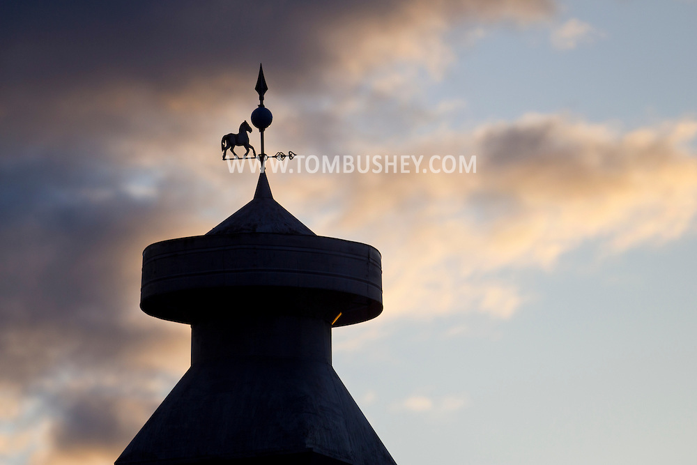 Goshen, New York - A weathervane with a horse on the roof of a barn at sunset on  April 27, 2014.