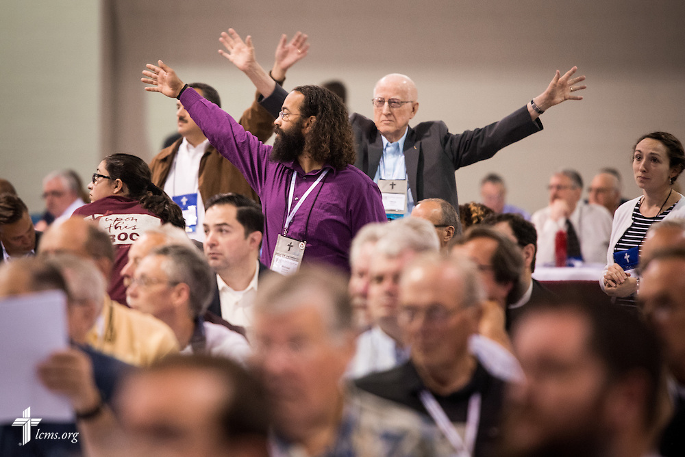Delegates either raise their hands or stand up to indicate they need a copy of an updated resolution on Monday, July 11, 2016, at the 66th Regular Convention of The Lutheran Church–Missouri Synod, in Milwaukee. LCMS/Frank Kohn