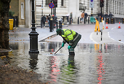 © Licensed to London News Pictures. 24/10/2019. London, UK. A worker attempts to unblock the drains on the roads near St James's Park in Westminster which flooded during a heavy downpour of rain. Photo credit: Ben Cawthra/LNP