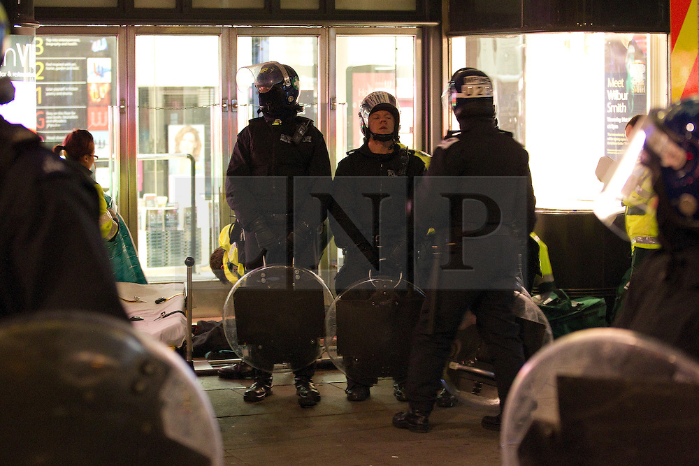 """© under license to London News Pictures. 25/03/2011: Police protect a fellow officer who lies injured on the ground, as paramedics attend to him. He was later taken aboard an ambulance. The officer was injured during large anticuts protests in Central London. Credit should read """"Joel Goodman/London News Pictures""""."""