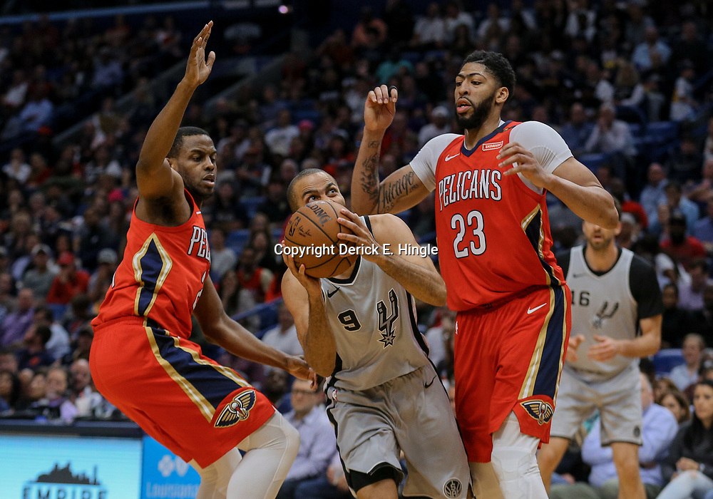 Apr 11, 2018; New Orleans, LA, USA; San Antonio Spurs guard Tony Parker (9) drives between New Orleans Pelicans forward Anthony Davis (23) and forward Darius Miller (21) during the second half at the Smoothie King Center. The Pelicans defeated the Spurs 122-98. Mandatory Credit: Derick E. Hingle-USA TODAY Sports
