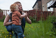 Victoria Cunningham blows a dandelion away with her baby Oliver-James Giles outside the house the family rents in Bradford, Great Britain Monday, May 26, 2014. Through Save the Children's EAT, SLEEP, LEARN AND PLAY programme the family was awarded a fridge freezer and a toy and book pack. A record five million children in the UK could be trapped in poverty by 2020, according to new research by Save the Children. The report reveals that children have paid the highest price in the recession, with families having been hit by years of flat wages, cut to benefits and the rising cost of living. (Elizabeth Dalziel for Save the Children )