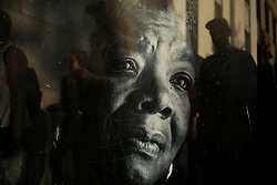 November 13, 2016 - Oakland, California, U.S - People walk past a bus stop poster of Maya Angelou on Oak Street near Lake Merritt where protestors were gathering to join hands in a peaceful protest against President-elect Donald Trump in Oakland, California. (Credit Image: © Joel Angel Ju'Ä°Rez via ZUMA Wire)