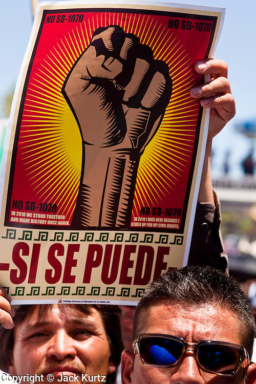 """May 29 - PHOENIX, AZ: A man holds up a si se puede (""""Yes We Can"""") sign at a pro-immigrant rights rally in Phoenix Saturday. More than 30,000 people, supporters of immigrants' rights and opposed to Arizona SB1070, marched through central Phoenix to the Arizona State Capitol Saturday. SB1070 makes it an Arizona state crime to be in the US illegally and requires that immigrants carry papers with them at all times and present to law enforcement when asked to. Critics of the law say it will lead to racial profiling, harassment of Hispanics and usurps the federal role in immigration enforcement. Supporters of the law say it merely brings Arizona law into line with existing federal laws.  Photo by Jack Kurtz"""