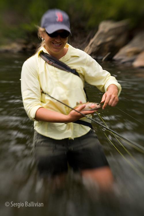 A woman enjoying flyfishing during summer on the Big Thompson River near estes Park Colorado.