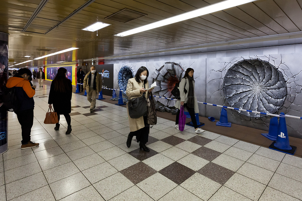 Three craters in a wall advertise the Jump Force video game for Play Station, X-box and Window PC in Shinjuku Station, Tokyo, Japan. Friday February 22nd 2019. Jump Force  game brings together all the most popular characters from the Shonan Jump manga comics.and was released on February 15th. The punch wall represents the effect of a power punch from characters Son Goku of Dragonball, Naruto and Luffy from One Piece and runs to February 24th