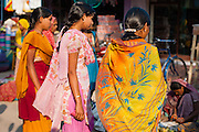 Indian women in saris shopping at local market (India)