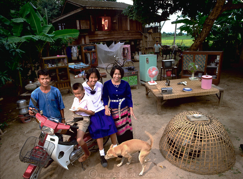 The Kuenkaew Family, 5:30 pm, May 31 1993, in front of their home with all of their possessions, Ban Muang Wa, Thailand. Published in Material World, pages 80-81. The Khuenkaews are a farming family that grows rice for personal use, and to sell for income. The Khuenkaew's live in a wooden 728-square-foot house on stilts, surrounded by rice fields.