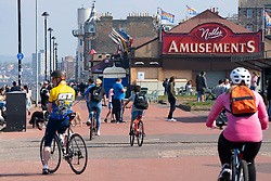 Portobello, Scotland, UK. 25 April 2020. Views of people outdoors on Saturday afternoon on the beach and promenade at Portobello, Edinburgh. Good weather has brought more people outdoors walking and cycling. The beach appears busy with possibly a breakdown in social distancing happening later in the afternoon. View along promenade showing people exercising. Iain Masterton/Alamy Live News