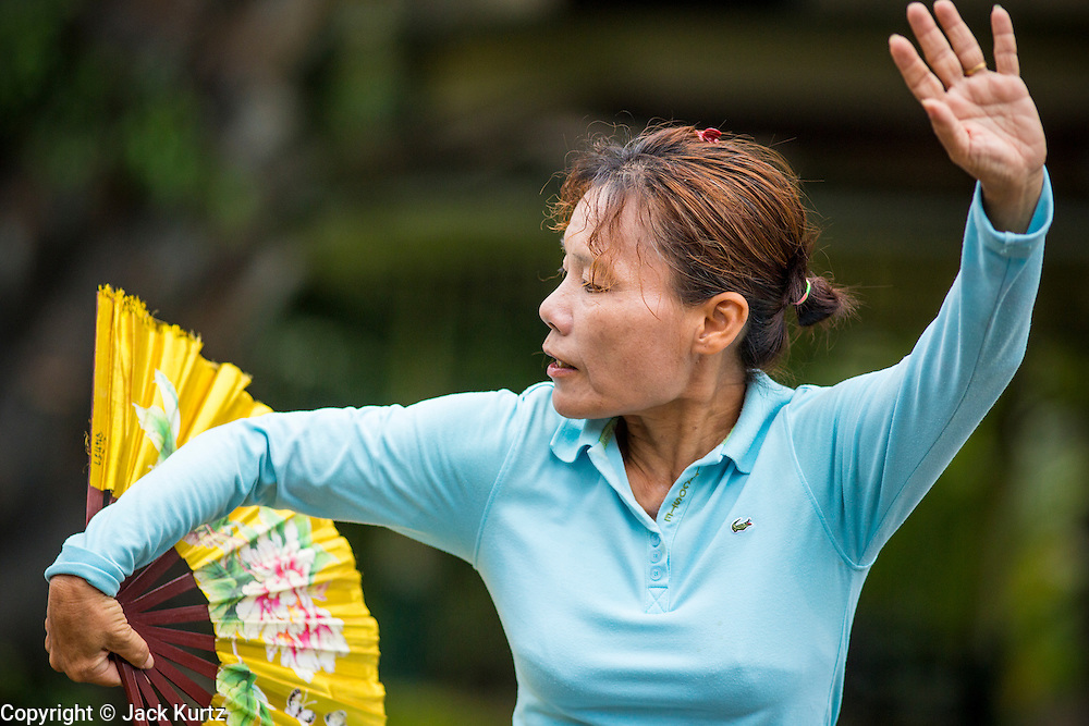 06 OCTOBER 2012 - BANGKOK, THAILAND:  A woman does Tai Chi exercises with a fan in Lumphini Park in Bangkok. The Thai government promotes exercise classes as a way staying healthy. Lumphini Park is 142 acre (57.6-hectare) park in Bangkok, Thailand. This park offers rare open public space, trees and playgrounds in the congested Thai capital. It contains an artificial lake where visitors can rent boats. Exercise classes and exercise clubs meet in the park for early morning workouts and paths around the park totalling approximately 1.55 miles (2.5km) in length are a popular area for joggers. Cycling is only permitted during the day between the times of 5am to 3pm. Smoking is banned throughout smoking ban the park. The park was created in the 1920's and named after Lumbini, the birthplace of the Buddha in Nepal.   PHOTO BY JACK KURTZ