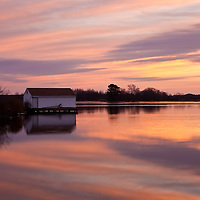 Sunrise and the refuge boathouse reflected in the waters of the Little Blackwater River, Blackwater National Wildlife Refuge, Cambridge, Maryland.
