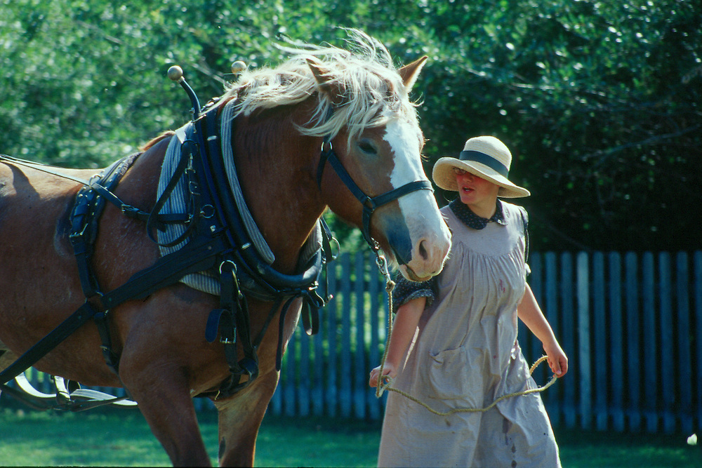 Farm girl in period costume leads horse, Motherwell Homestead National Historic Site, Saskatchewan