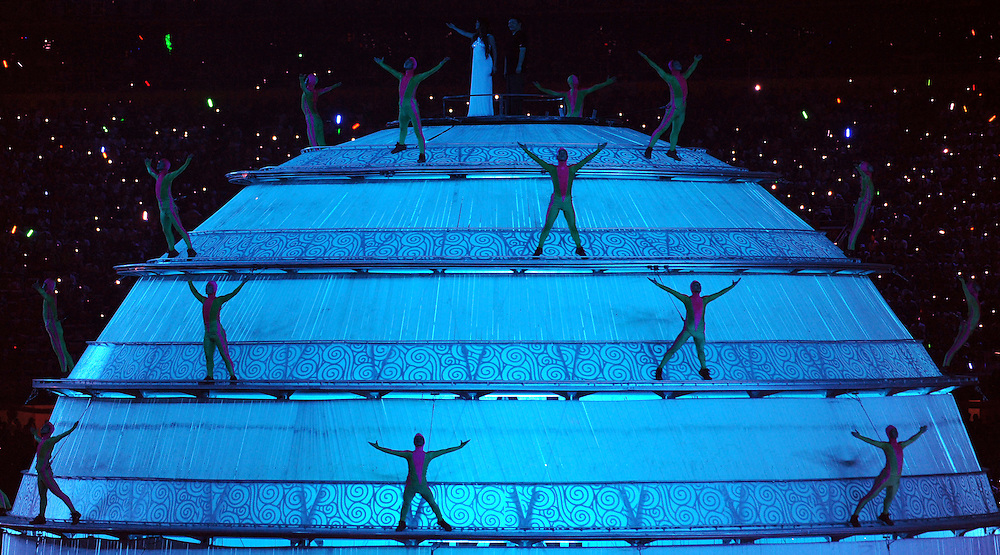 """2008 OLYMPIC GAMES - OPENING CEREMONIES - 080808 - Acrobats circle a large glowing globe during the Opening Ceremonies as two singers on top of the globe perform the theme song, """"You and Me""""."""