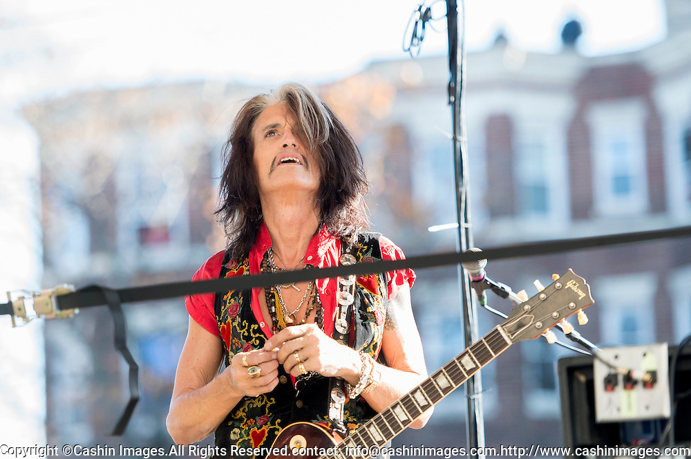05 November 2012:  Aerosmith's Joe Perry looks up to fans in the window of his old apartment during a free concert in Boston's Allston neighborhood in front of the apartment building, 1325 Commonwealth Ave, which was the band's home in the early 1970's.  Boston, MA. ***Editorial Use Only*****