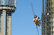 A construction worker installs rebar at the top of the Omni hotel in downtown Dallas. Reunion Tower is seen at left.