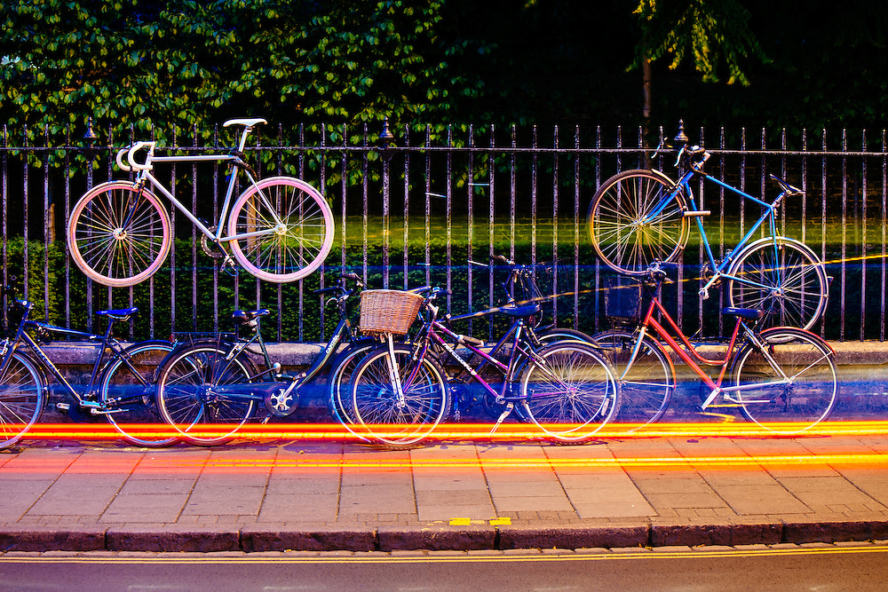 Bicycles attached to a fence along a street in Cambridge, UK.