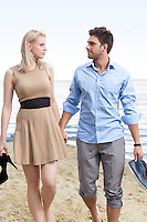 Romantic young couple holding hands and walking on beach
