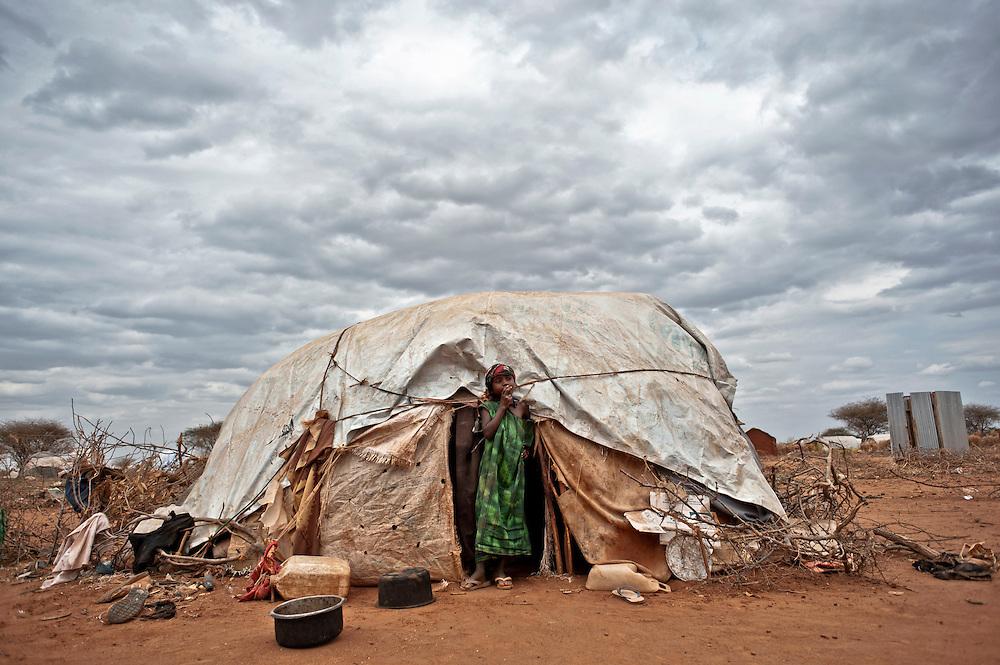Camp Ifo III. Une petite fille, devant l'abri familial installé en périphérie du camp. Le ciel chargé annonce une pluie orageuse qui ne viendra jamais. La région n'a connu aucune précipitation depuis 3 ans. La tente n'est pas enregistrée par le UNHCR, là où elle est située, les ONG craignent d'imminentes inondations, sources d'épidémies. L'eau ne pénètre plus la terre trop aride et emporterait les habitations aux premières averses. A droite, les latrines encore trop peu nombreuses desservent à elles seules près de 15 familles.