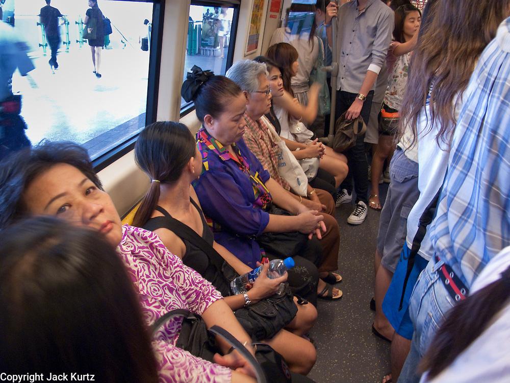 """09 OCTOBER 2009 -- BANGKOK, THAILAND: Passengers on the Sukhumvit line of the Bangkok """"Skytrain,"""" BTS system. PHOTO BY JACK KURTZ"""