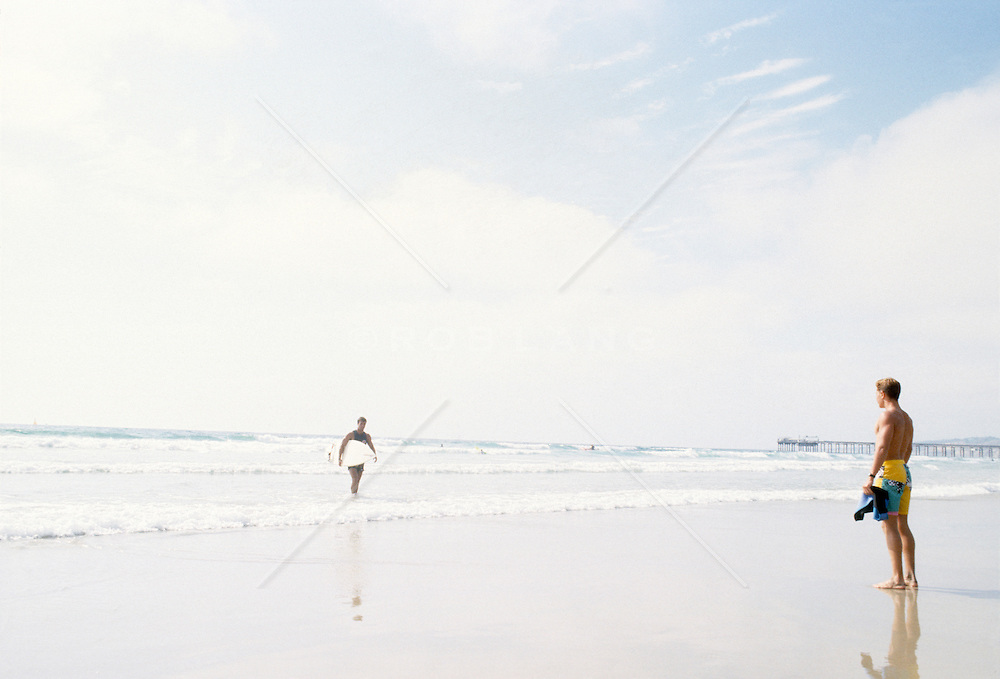 Surfer coming out of the ocean while a muscular man stands on the shore looks on.