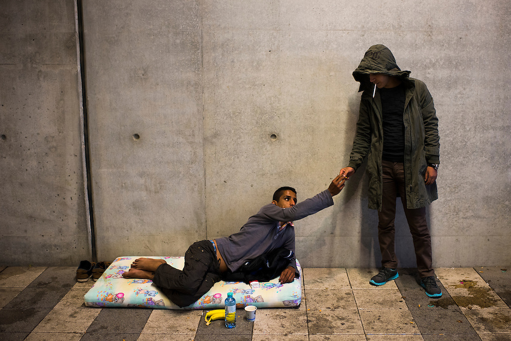 Syrian migrants, who are hoping to reach London, share cigarettes at Wien Hauptbahnhof train station on September 22, 2015 in Vienna, Austria.