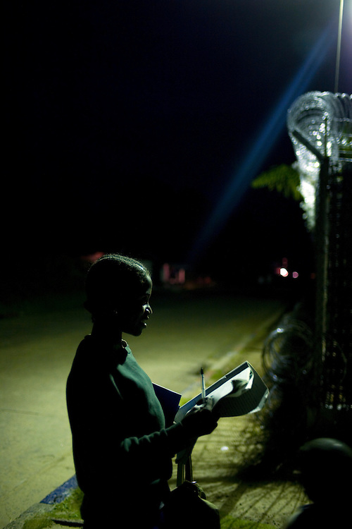 Girls doing their home work under one of the few working street lights in Buchanan, Liberia. Martha 14 years old in 6th grade.