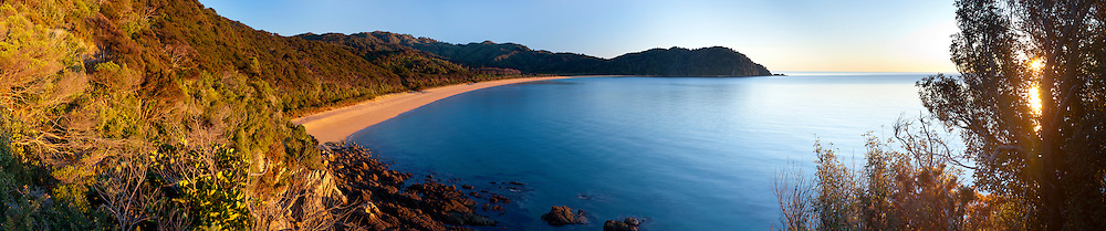 A panoramic view of Totaranui Beach at sunrise on a clear morning. Abel Tasman National Park, New Zealand.