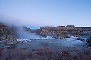 View of spray from behind Shoshone Falls during spring run off, high water, at sunrise.  Southern Idaho.