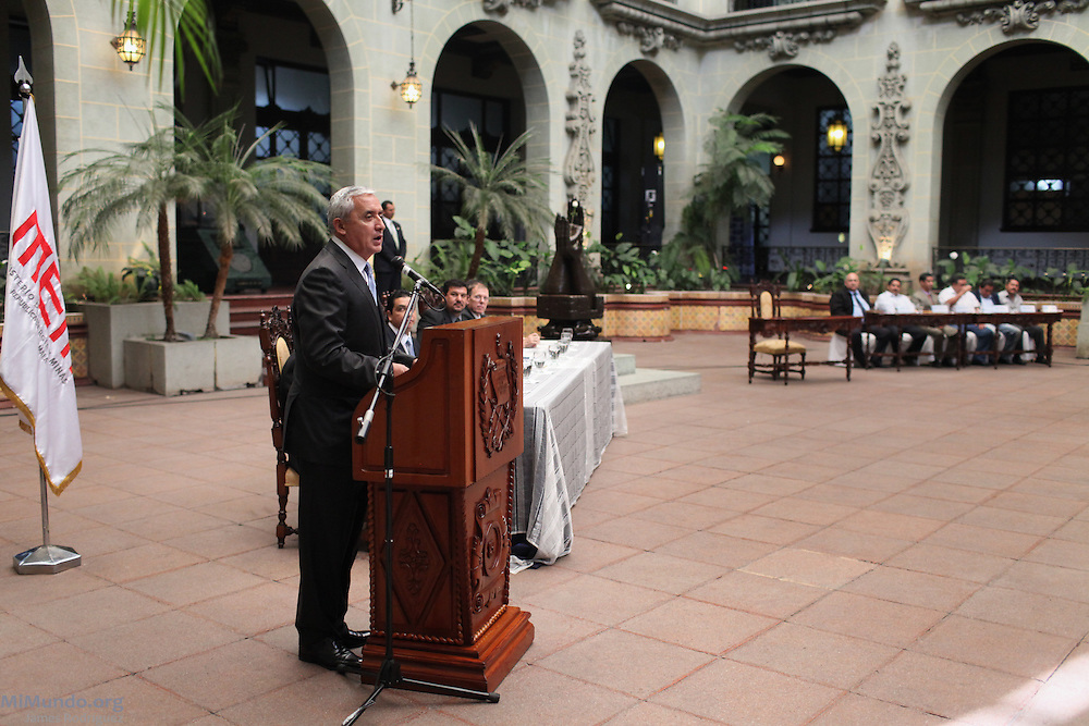 President Otto Perez Molina speaks during the signing of the official convene between the Guatemalan government and Tahoe Resources & Goldcorp's El Escobal silver project via its local subsidiary Minera San Rafael. Six mayors from adjacent municipalities that will receive a voluntary subsidy from the mine sit in the far table. The signing comes two days after six locals were shot by the company's security guards. Since 2011, eight local communities have carried out plebiscites that have rejected nearly unanimously the mining project in San Rafael Las Flores, Santa Rosa. Guatemala City, Guatemala. April 29, 2013.