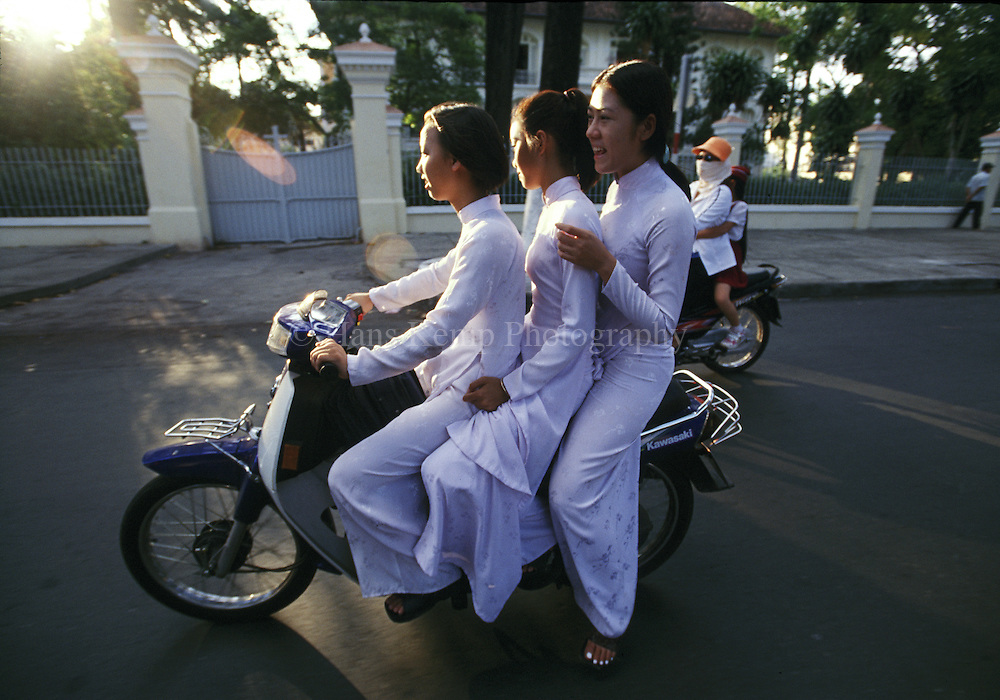 Schoolgirls wearing the traditional Au Dai, on the way to school in Saigon, Vietnam
